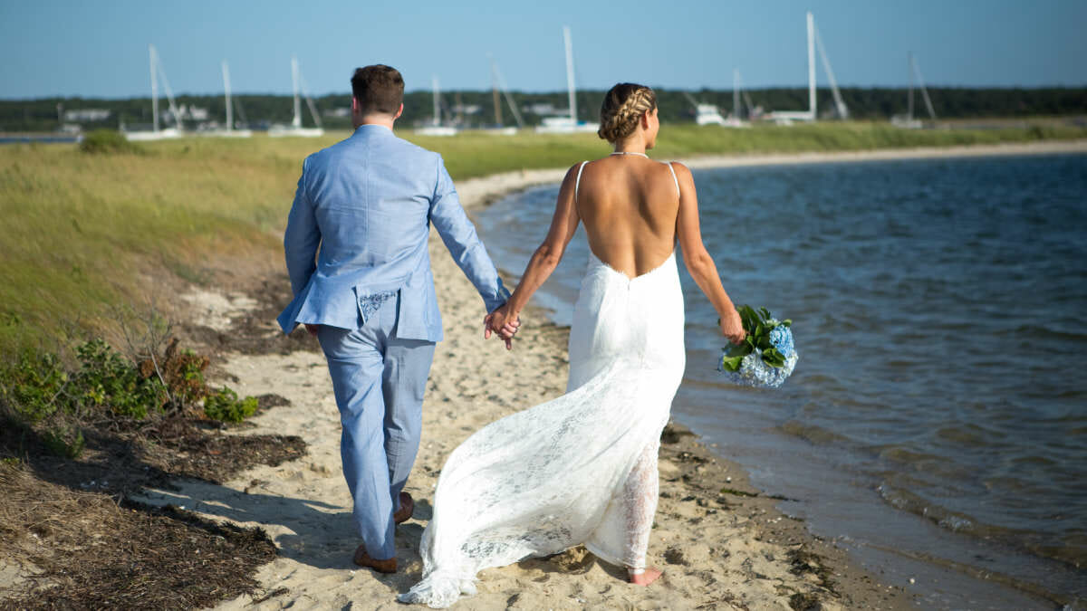 Bride and groom walking along the beach holding hands