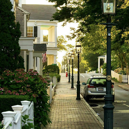 A quiet street on martha's Vineyard aligned with street lights and a car.