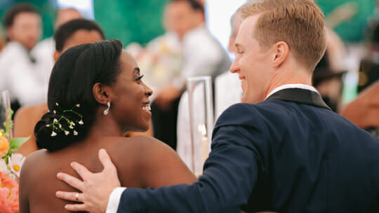 Wedding couple sitting at a table smiling at each other