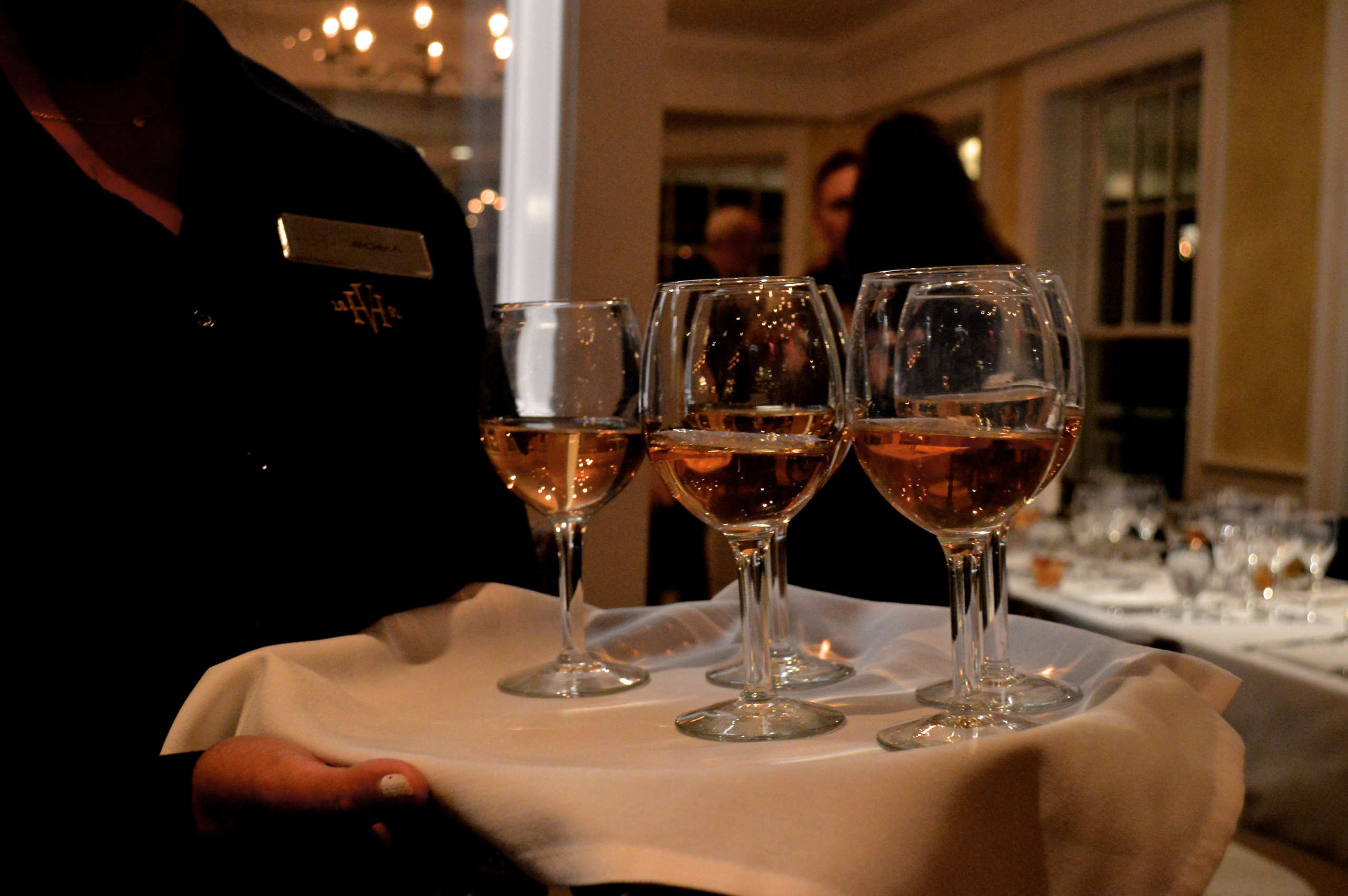A server holding a tray of wines for a wine tasting in Bettini Restaurant.