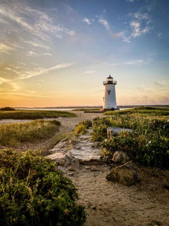 Lighthouse on the beach at sunset