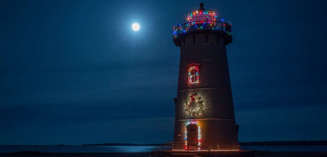 Lighthouse decorated in Christmas lights light up at night