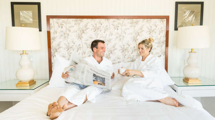 Couple lounging in bed with ropes on reading the paper and drinking coffee