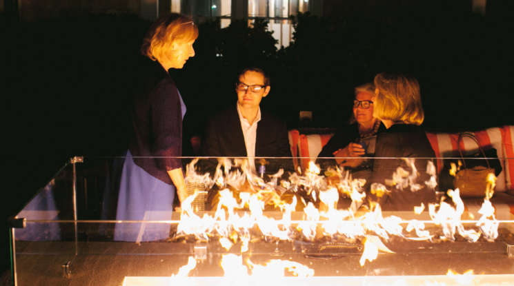 Guests chatting by the fire pit at night