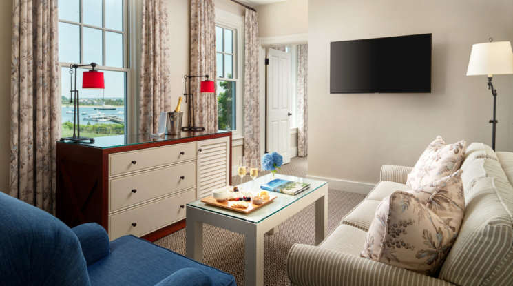 Living room in a room suite with couch, table, chair, and TV