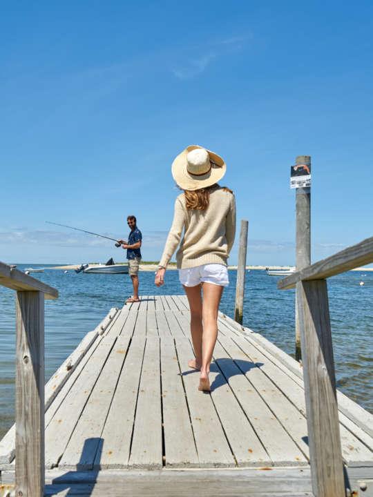 Woman walking on a dock toward her husband fishing