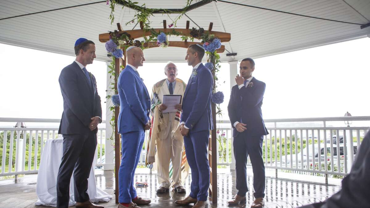 Four men standing in blue suits on the gazebo