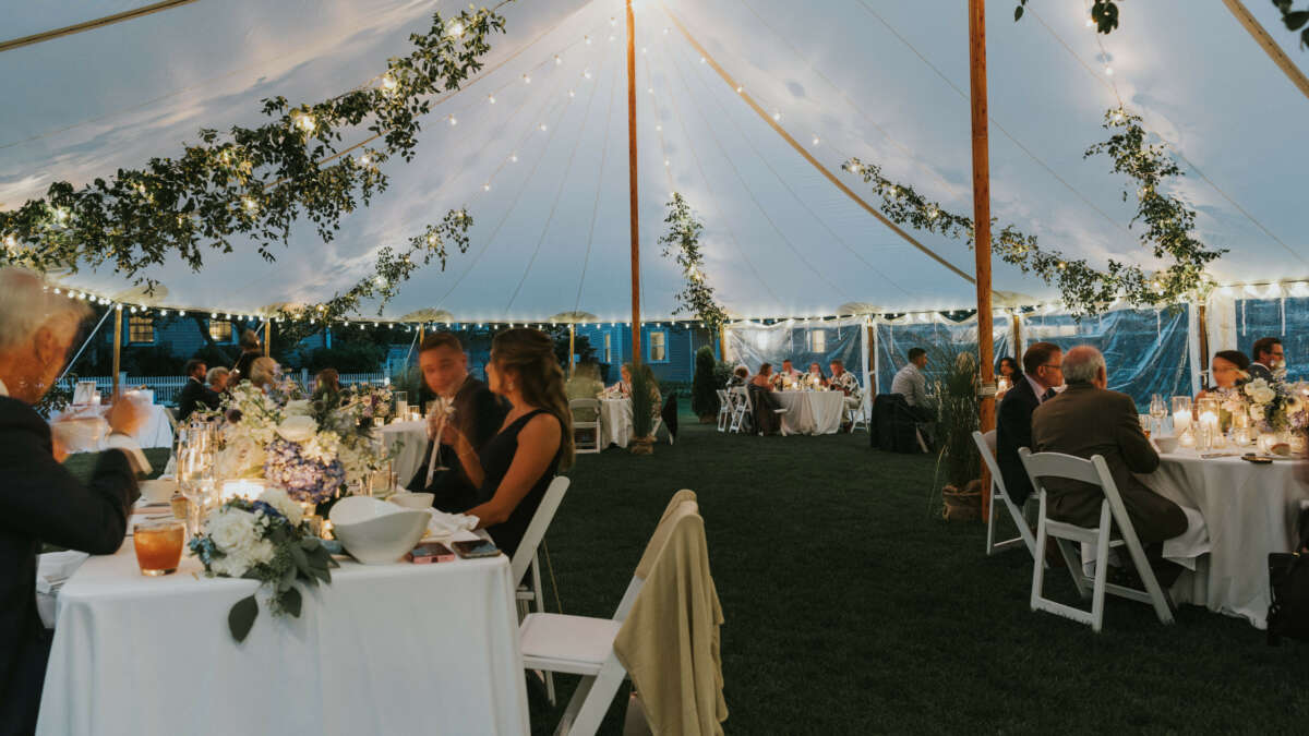 a tent with tables and guests sitting at the tables