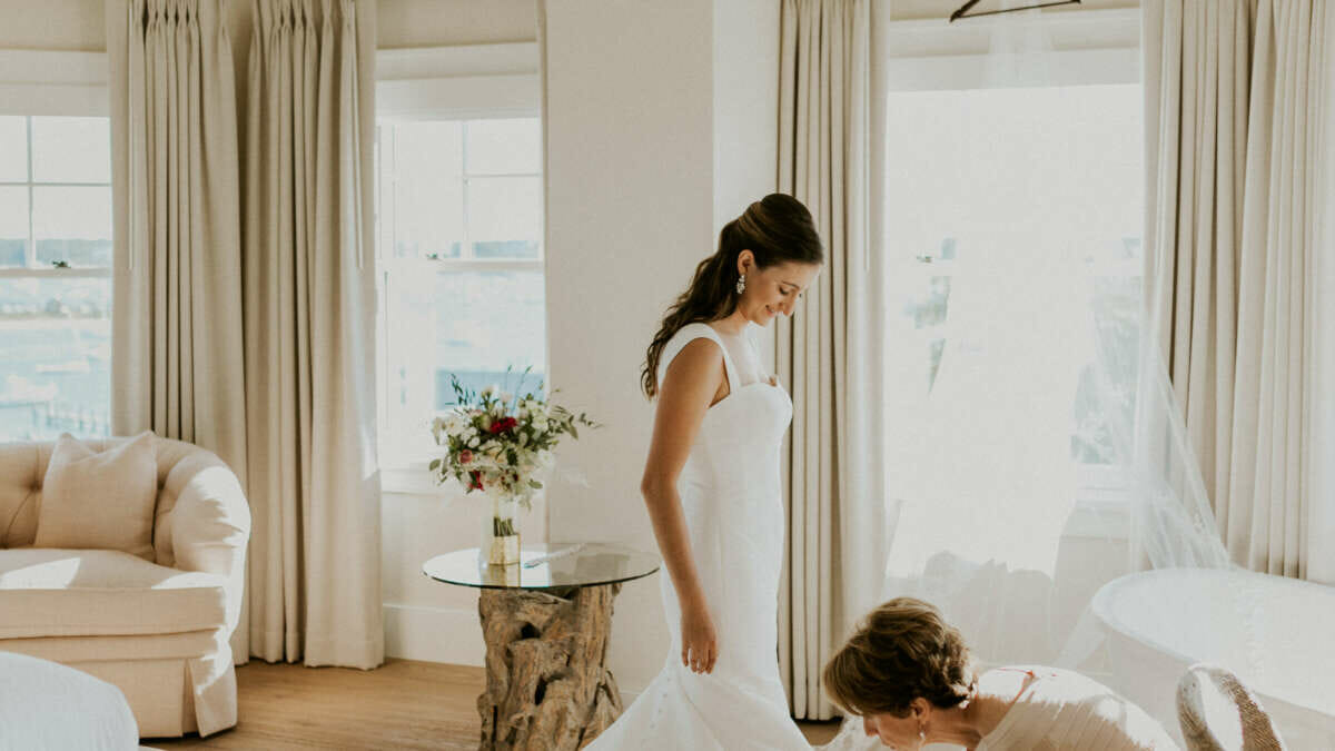 a bride in a white dress and train in a room