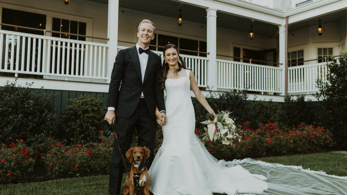 A man, woman in a wedding dress, and a brown dog on the lawn