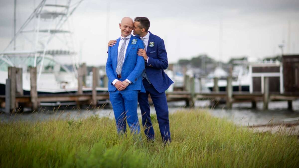 two men holding each other in blue suits