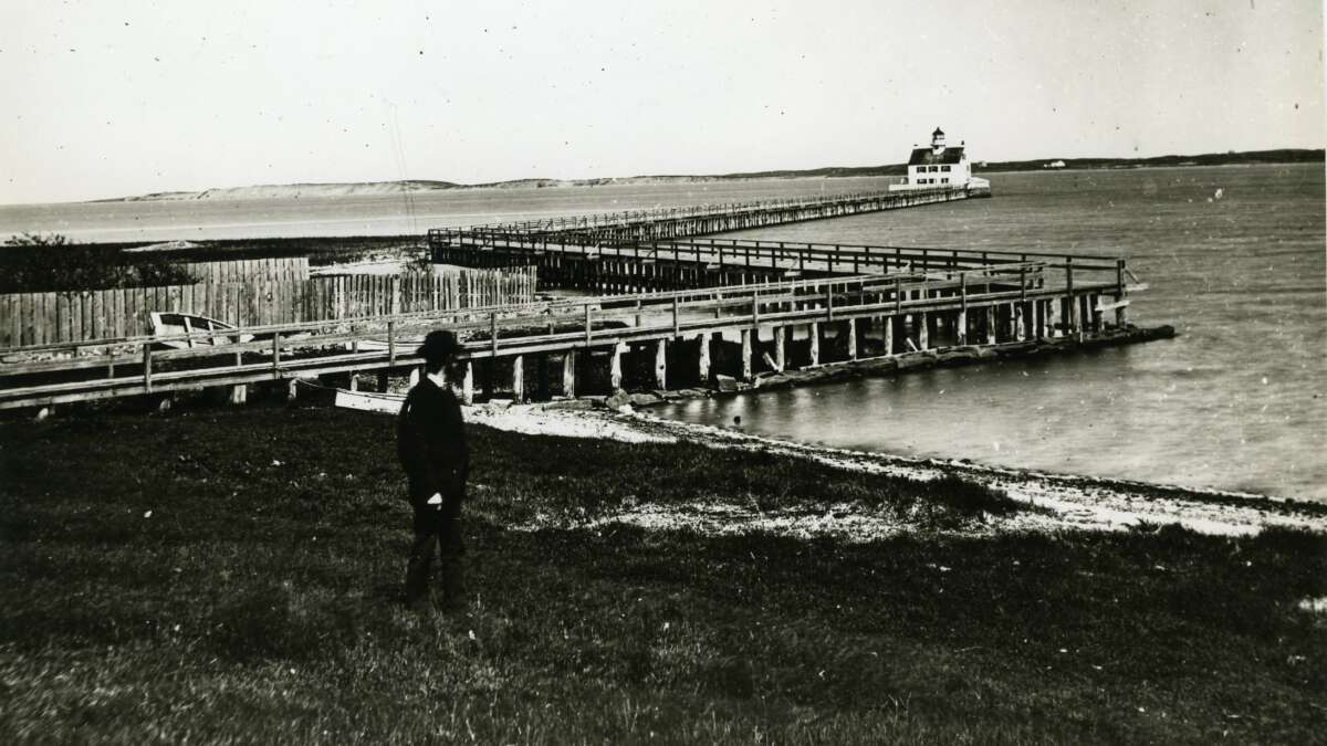 boardwalk and lighthouse in a black and white photo