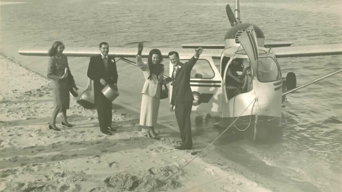 A black and white photo of people on a beach and a small airplane in the water