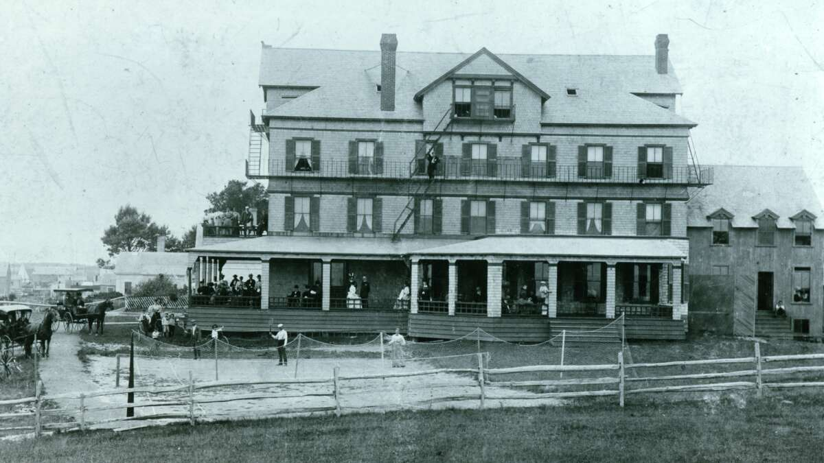 A black and white photo of the harborview hotel with people on the veranda