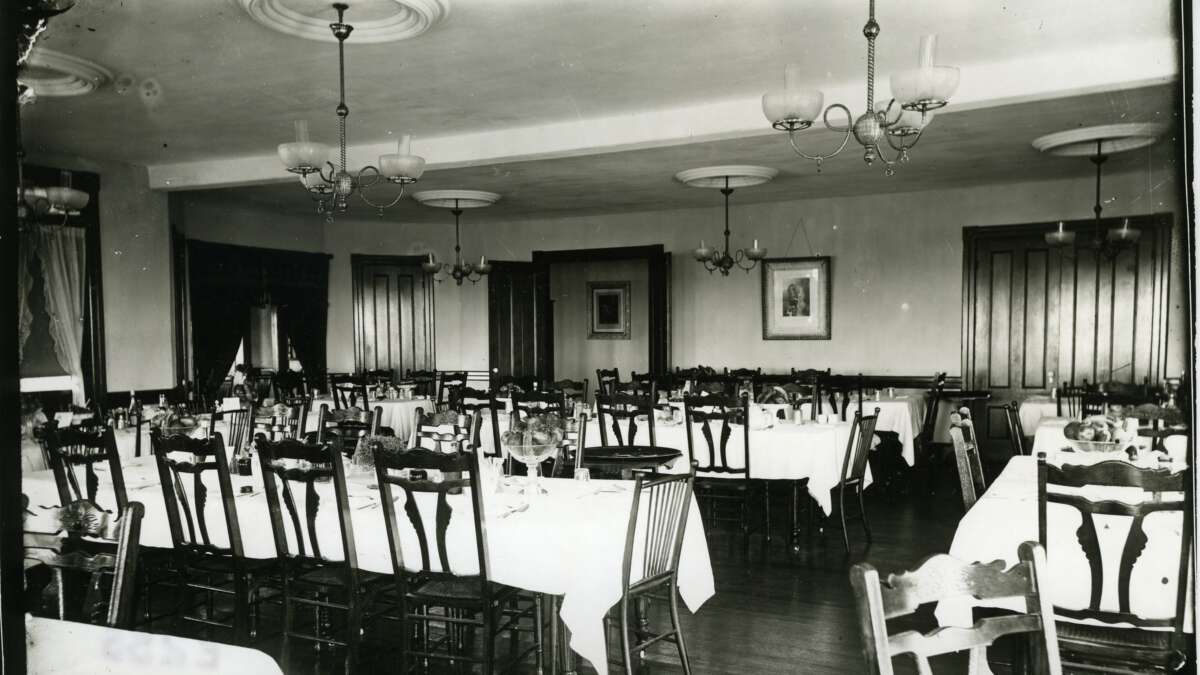 A black and white photo tables and chairs in a dining setting