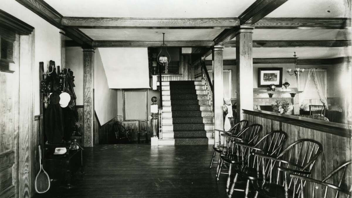 A black and white photo with wooden chairs lined up and a staircase