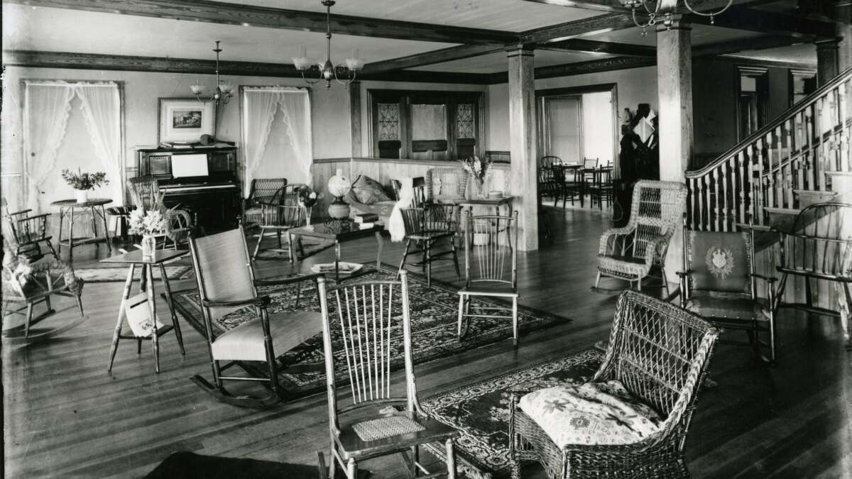 A black and white photo of a the lobby with wicker chairs