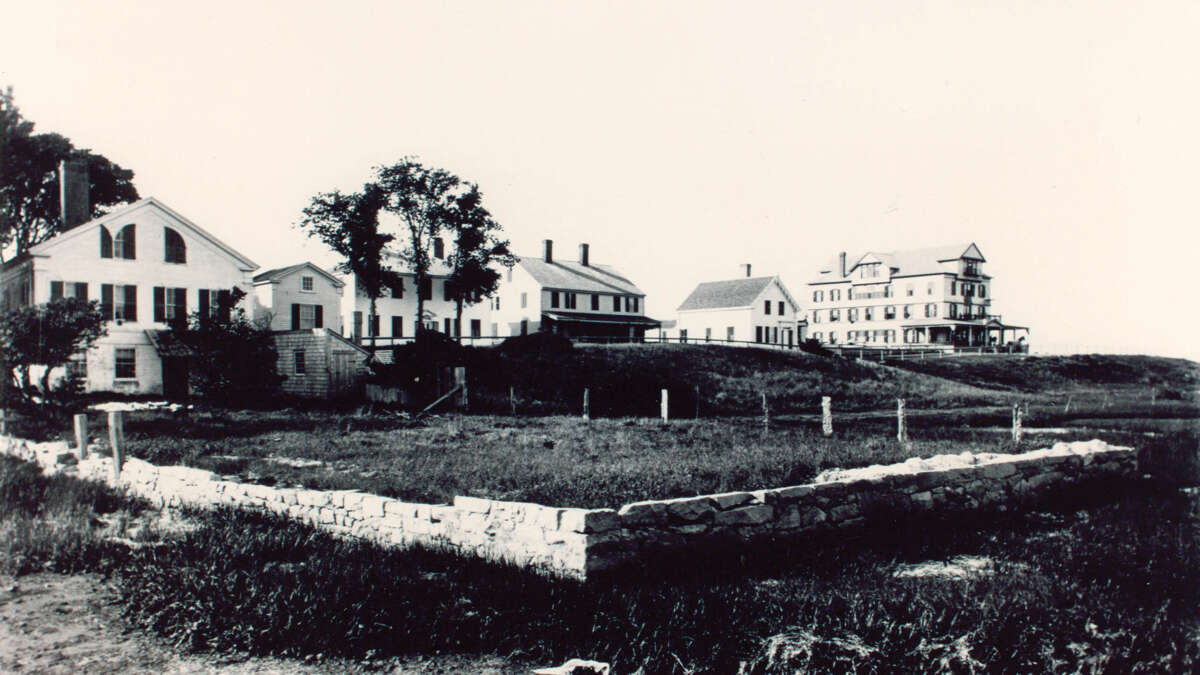 A black and white photo of houses and harbor view hotel lining a street