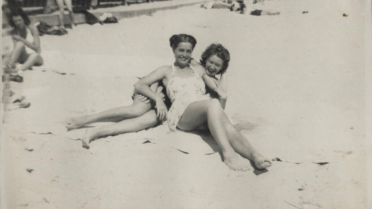 A black and white with two ladies on the beach