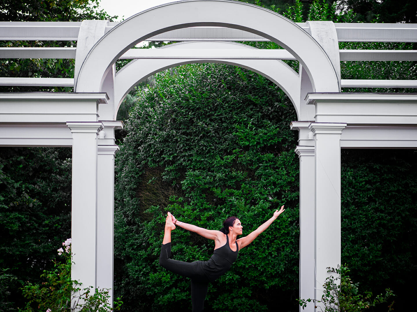 a woman in a yoga pose under an arch