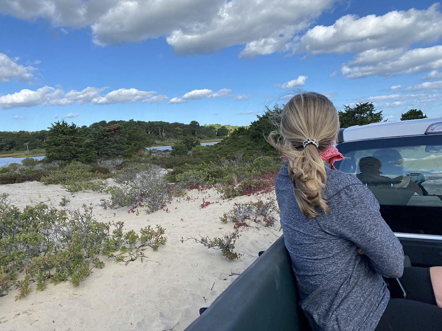 a woman sitting in a truck looking at ocean